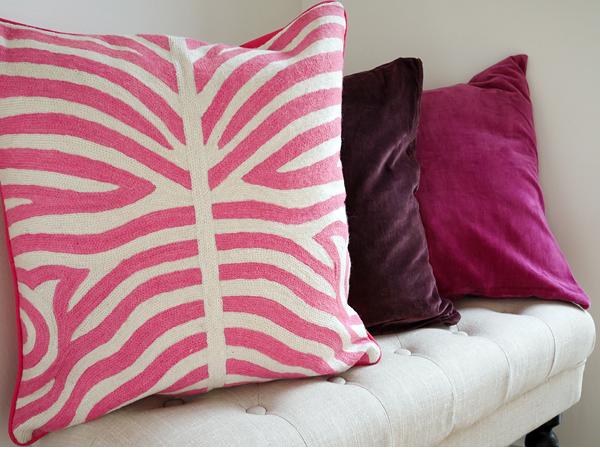Foto Longcoast Living. Handbroderat rosa kuddfodral i zebramönster från Chamois. Enfärgade sammetskuddar i rosa och plommonlila.